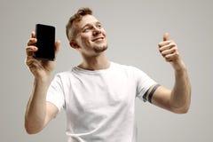 Młody przystojny mężczyzna pokazuje smartphone ekran odizolowywającego na szarym tle w szoku z niespodzianki twarzą fotografia stock
