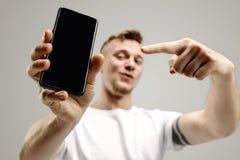 Młody przystojny mężczyzna pokazuje smartphone ekran odizolowywającego na szarym tle w szoku z niespodzianki twarzą zdjęcie royalty free