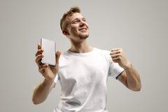 Młody przystojny mężczyzna pokazuje smartphone ekran odizolowywającego na szarym tle w szoku z niespodzianki twarzą obrazy royalty free