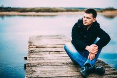 Młody przystojny mężczyzny obsiadanie na drewnianym molu, relaksujący, myśleć, słuchający Przypadkowy styl - cajgi, kurtka zdjęcie royalty free