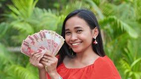 Młody szczęśliwy dziewczyny mienie w ona ręka indonezyjczyka pieniądze Sukces pojęcie zbiory