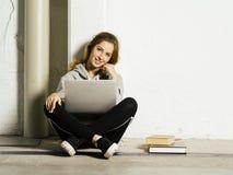 Młody szczęśliwy studencki działanie na jej laptopie w szkolnym korytarzu obrazy royalty free