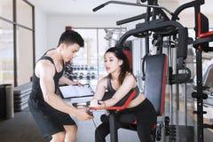 Młody trener pomaga jego klienta trenować w gym fotografia stock
