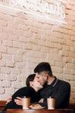 Młody uroczy pary całowanie podczas gdy siedzący w kawiarni zdjęcie stock