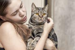 Młodych caucasian kobieta chwytów krótkiego włosy brytyjski kot z jaskrawymi żółtymi oczami, obejmuje je fotografia royalty free
