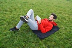 Młodzi człowiecy używa cyfrowego pastylka parka publicznie zdjęcia royalty free