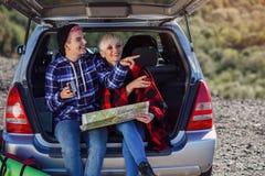 Młodzi przyjaciół podróżnicy siedzi na bagażniku samochód z nakrętką herbaciany i patrzeje papierową mapę Dwa szczęśliwej modniś  obrazy stock