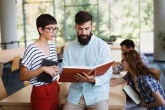 Młodzi szczęśliwi ucznie siedzi w bibliotece obraz royalty free