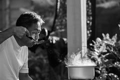 Mål för mat för gamal manmatlagningmorgon i varm kruka på LPG-gasugnen Arkivbild