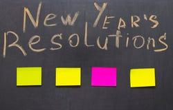 Mål för nytt år eller upplösningar - klibbiga anmärkningar på en svart tavla Arkivbild