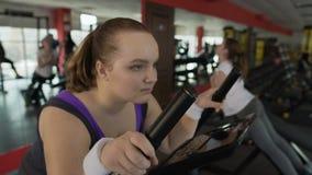 Mål-orienterad överviktig kvinna som övar på den stationära cykeln som hårt arbetar stock video