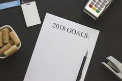 2018 mål skyler över brister, en bunke av kakor och kontorstillförsel Royaltyfri Foto