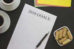2018 mål skyler över brister med kaffekoppar, en penna och en bunke av kakor Royaltyfri Fotografi