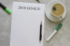 2018 mål skyler över brister, pennor, kaffekopp med tefatet Arkivbild
