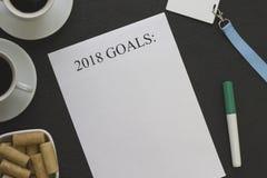 2018 mål skyler över brister, två kaffekoppar med tefat, en bunke av kakor och kontorstillförsel Royaltyfria Foton