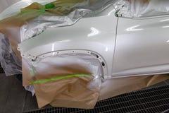 Måla den vita bilen SUV i seminariet för kroppreparation Bil som täckas med papper arkivbilder