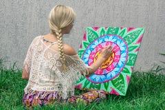 Måla det fria, drar en blondin för ung kvinna en mandala på naturen som sitter i gräset royaltyfri foto