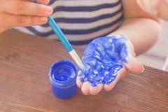Måla din hand med grön målarfärg Ett barn målar gömma i handflatan målarfärg, c fotografering för bildbyråer