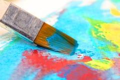 Måla en bild på ett papper med en borste Arkivfoto