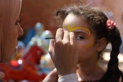 Måla för kvinna pojkar vänder mot på välgörenhethändelsen Royaltyfria Foton