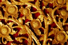 Måla guld- snida för blomma som och lokalt för prydnad för röd bakgrund är trä med thailändsk stildesign Fotografering för Bildbyråer