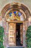 Måla ingången till San Michele kyrktaga i San Candido Arkivfoto