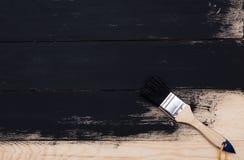Måla naturligt trä med målarfärgborsten Arkivfoto