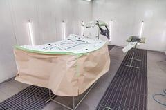Måla och torka i en yrkesmässig ask av bilkroppsdelar, når att ha applicerat spackel och målarfärg på den inre sidohuven i kroppr royaltyfri bild