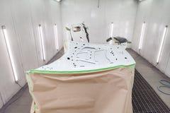 Måla och torka i en yrkesmässig ask av bilkroppsdelar, når att ha applicerat spackel och målarfärg på den inre sidohuven i kroppr arkivbild