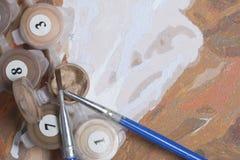 Måla på kanfas vid nummer Numrerade behållare med målarfärger och borstar ligger på kanfasbakgrunden Royaltyfria Bilder