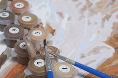 Måla på kanfas vid nummer Numrerade behållare med målarfärger och borstar ligger på kanfasbakgrunden Arkivfoton