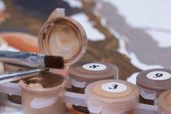 Måla på kanfas vid nummer Numrerade behållare med målarfärger och borstar ligger på kanfasbakgrunden Arkivbild