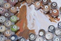 Måla på kanfas vid nummer Numrerade behållare med målarfärger och borstar ligger på kanfasbakgrunden Fotografering för Bildbyråer