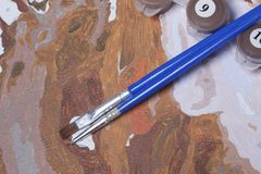 Måla på kanfas vid nummer Numrerade behållare med målarfärger och borstar ligger på kanfasbakgrunden Arkivbilder