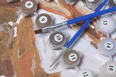 Måla på kanfas vid nummer Numrerade behållare med målarfärger och borstar ligger på kanfasbakgrunden Arkivfoto