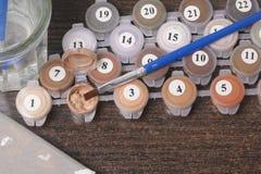 Måla på kanfas vid nummer Numrerade behållare med målarfärger och borstar ligger på kanfasbakgrunden Royaltyfri Bild