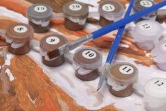 Måla på kanfas vid nummer Numrerade behållare med målarfärger och borstar ligger på kanfasbakgrunden Royaltyfri Fotografi