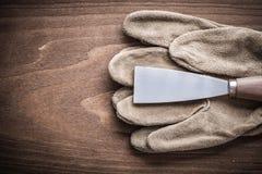 Måla skrapan och den funktionsdugliga handsken på det wood brädet Arkivfoto