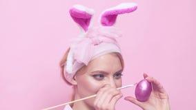 Måla upp äggslut Älskvärd retro kvinna i kanindräkt Lycklig kvinna i kanin?ron med det easter ?gget roliga easter lager videofilmer