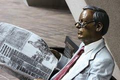 Målad bronsstaty av en man som läser en tidning arkivbild