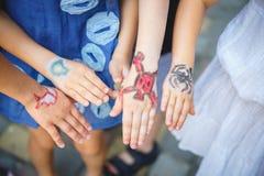 Målad children& x27; s-händer i olika färger med smilies Arkivbild