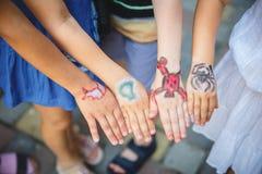 Målad children& x27; s-händer i olika färger med smilies Arkivfoto