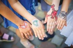 Målad children& x27; s-händer i olika färger med smilies Fotografering för Bildbyråer