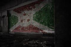 Målad flagga av Burundi på den smutsiga gamla väggen i ett övergett förstört hus royaltyfria bilder