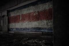 M?lad flagga av Costa Rica p? den smutsiga gamla v?ggen i ett ?vergett f?rst?rt hus royaltyfria bilder