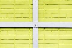 Målad gul textur för tegelstenvägg, vit fyrkantig ram för metall, tvärbommar, stads- bakgrund, utrymme för text Royaltyfria Foton