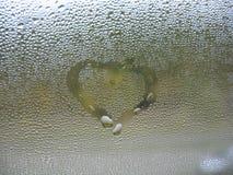 Målad hjärta på droppar för fönsterexponeringsglas och regn Arkivbild