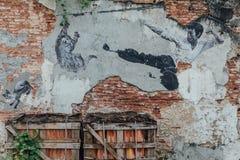 Målad kinesisk katt för manbanhoppningspark i luften på den gamla väggen för röd tegelsten från gatan av George Town malaysia pen royaltyfria foton