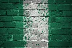 Målad nationsflagga av Nigeria på en tegelstenvägg Arkivfoto