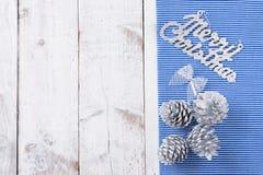 Målad snö sörjer kottar på den lantliga vita wood tabellen Royaltyfri Foto